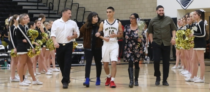 Senior Joey Stowers, accompanied by family members, on Senior Night.
